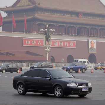 An Audi car drives past Tiananmen Square as a police officer stands guard on a street in central Beijing