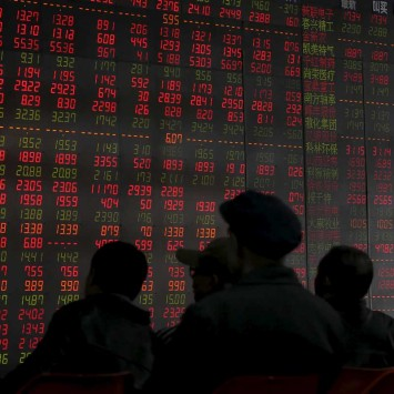 Investors look at an electronic board showing stock information at a brokerage house in Shenyang