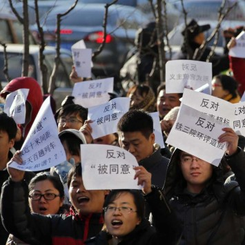 Locals hold signs during a protest against the construction of a new high speed railway from Beijing to Shenyang, in Chaoyang district, Beijing