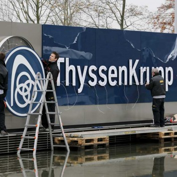 Electricians carry a cover with the logo of ThyssenKrupp AG at the company's headquarters in the western German city of Essen