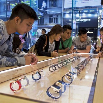 Customers look at Apple Watches after the device went on display at an Apple Store in Hong Kong