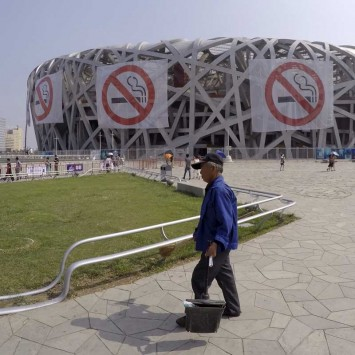 "A cleaner stands in front of giant ""No-smoking"" signs on the exterior of the National Stadium, also known as the Birds' Nest, as part of an anti-smoking campaign, in Beijing"