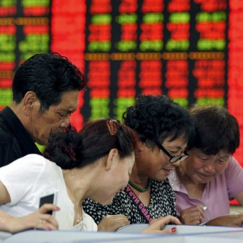 Investors look at computer screens in front of an electronic board showing stock information at a brokerage house in Fuyang