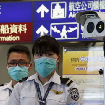 Airport staff stand by to wait for arriving passengers to conduct a temperature check at Hong Kong Airport in Hong Kong