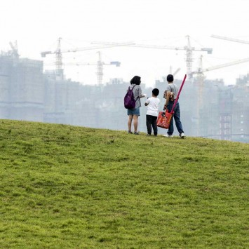 A family stands on an artificial grassland near a construction site of a residential complex, in Hefei