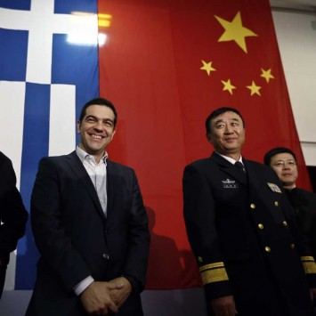 Greek PM Tsipras smiles in front of a Greek national flag and a Chinese national flag before his speech aboard the Chinese frigate Changbaishan at the port of Piraeus, near Athens