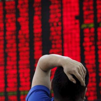 A man watches a board showing stock prices at a brokerage office in Beijing,