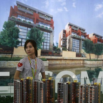 A sales agent waits for customer in front of the model of a property development at the 5th China (Shenzhen) Real Estate Fair, in the southern Chinese city of Shenzhen