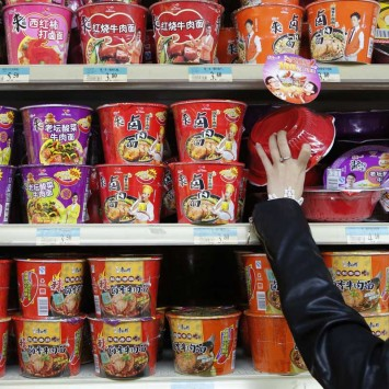 A woman chooses a cup noodle from at a supermarket in Beijing