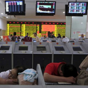 Investors rest in front at computer screens at a brokerage in Shanghai