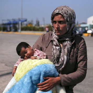 A Syrian refugee holds her baby following their arrival onboard the Eleftherios Venizelos passenger ship at the port of Piraeus, near Athens