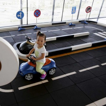 A girl rides a toy car at the VIP lounge of BMW dealer shop in Beijing