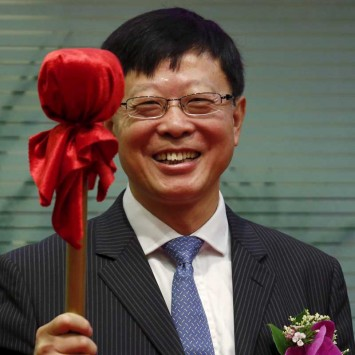 China International Capital Corp Chairman Ding Xuedong smiles before hitting a gong during the debut of CICC at the Hong Kong Stock Exchanges in Hong Kong