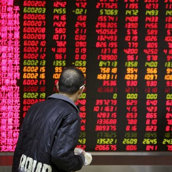 An investor walks past in front of an electronic board showing stock information at a brokerage house in Beijing