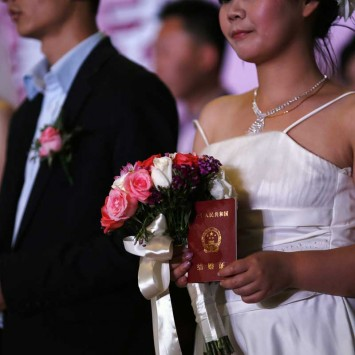 A woman holds her marriage certificate, as couples participate in a staged mass wedding in Shanghai