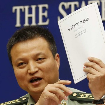 Spokesperson of Chinese Ministry of National Defense Senior Colonel Yang holds a copy of the annual white paper on China's military strategy during a news conference in Beijing