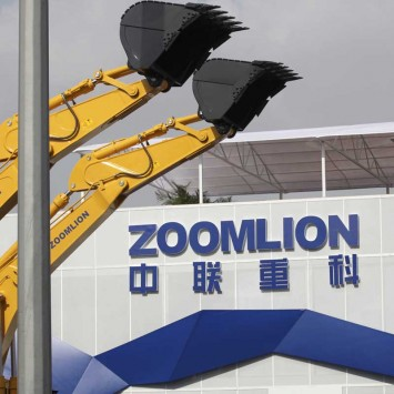 A Zoomlion company logo is seen next to its excavators at an exhibition in Shanghai