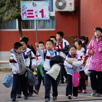 A student holds a placard showing the name of his class as he leaves school with his classmates at an elementary school in Beijing