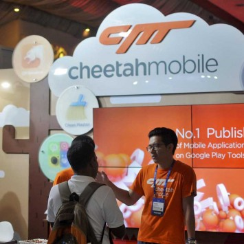 "A visitor listens to a briefing by employees of China's Cheetah Mobile at the company's information kiosk at ""Surge 2016"" in Bengaluru"