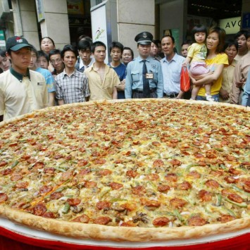 RESIDENTS LOOK AT A GIANT PIZZA WITH A DIAMETER OF 2 METERS.