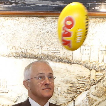 Australian Prime Minister Malcolm Turnbull watches a rugby ball fly past Gui Guojie, general manager of Shanghai CRED Real Estate Stock, after a signing of the memorandum of understanding at a hotel in Shanghai