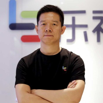 Jia Yueting, co-founder and head of Le Holdings Co Ltd, poses for a photo in front of a logo of his company in Beijing