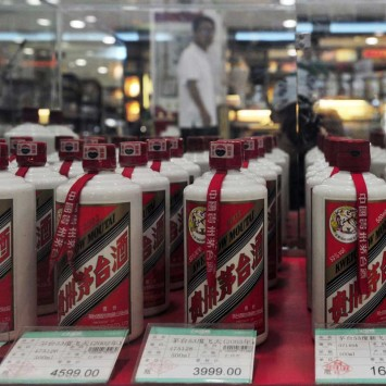 A customer walks past a glass case displaying Maotai liquors with different price tags at a supermarket in Shenyang