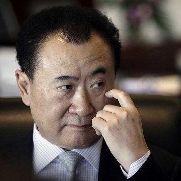 Wang, chairman of Dalian Wanda Group, touches his face during an interview at his office in the company's headquarters in Beijing