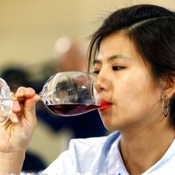 A wine expert from China tests a Chinese red wine during a testing session at the 50th Vinitaly international wine and spirits exhibition in Verona