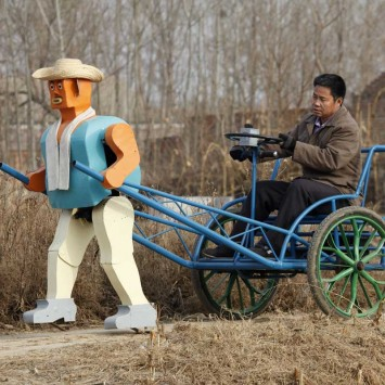 Farmer Wu Yulu drives his rickshaw pulled by a his self-made walking robot in Beijing
