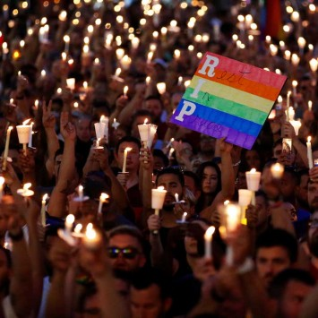 People take part in a candlelight memorial service the day after a mass shooting at the Pulse gay nightclub in Orlando