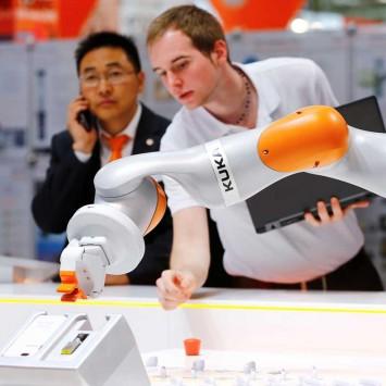 A Kuka technician programs a robot arm of German industrial robot maker Kuka in Hanover