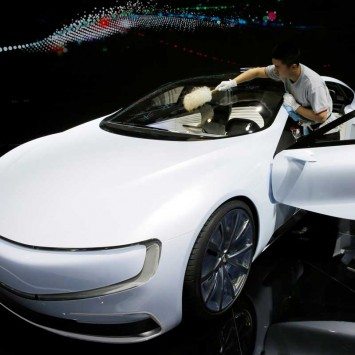 A member of staff brushes off dust from all-electric battery concept car called LeSEE during Auto China 2016 auto show in Beijing