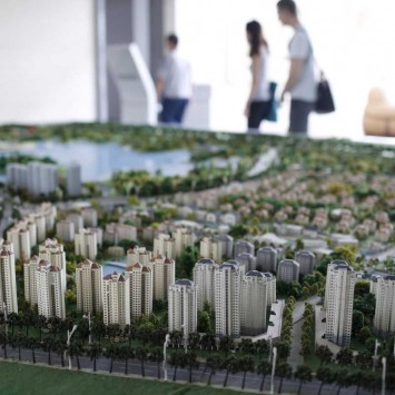 People walk past behind a miniature model of the Jiyanghu Ecological Park at a showroom in Zhangjiagang