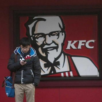 A man checks on his mobile phone outside a KFC restaurant in Shanghai