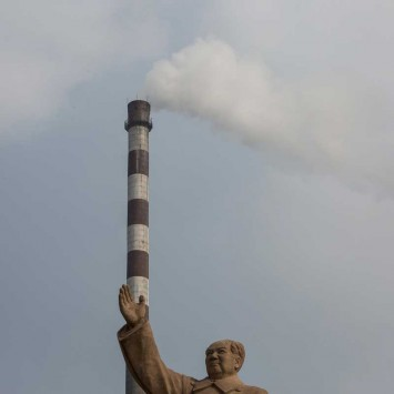 A statue of former Chinese leader Mao Zedong is seen in front of smoking chimney at a petrochemical plant in Nanjing