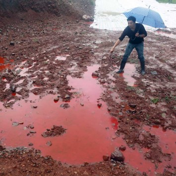 A man points to water and soil which turned red after being contaminated by industrial waste from a closed dye factory, amid heavy rainfall at a mountain in Ruyang county