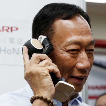 Terry Gou, chairman of Hon Hai Precision Industry, better known as Foxconn, tries Sharp Corp's RoBoHon, a humanoid communication robot-shaped mobile phone, at a Sharp showroom in New Taipei City