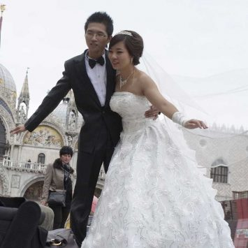 A wedding couple from China pose for a photographer in front of the San Marco Dome at Piazza San Marco in Venice