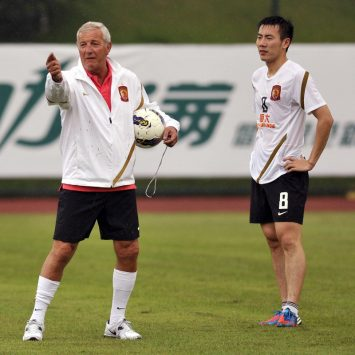 Coach Marcello Lippi gestures as Guangzhou Evergrande football club team member Qin Sheng stands next to him during a training session after a signing ceremony during a rainy day in Guangzhou