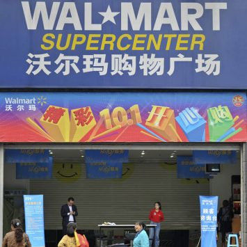 Employees stand in front of the gate to a Wal-Mart Supercenter in Chongqing municipality